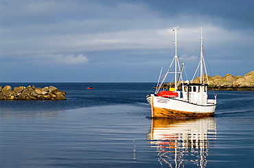 Small fishing boat arrives in harbor, Stamsund, Lofoten islands, Norway