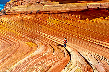 Hikers exploring The Wave, a 190 million year old Jurassic-age Navajo sandstone rock formation, Coyote Buttes, Paria Canyon-Vermillion Cliffs Wilderness Area, Utah-Arizona border, USA