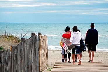 A family walking to the beach. Due to the economic crisis many families have chosen to take vacations at the inexpensive Mediterranean beaches of France's Herault.
