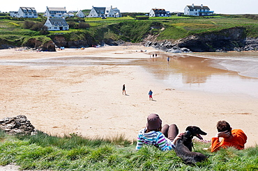 Europe, UK, England, Cornwall - Two people and their dog on the low cliffs behind the blue flag beach at Treyarnon Bay near Padstow.
