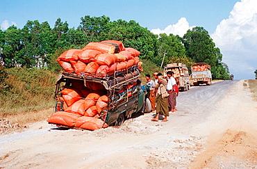 Pickup truck stuck in a big pot hole, Burma