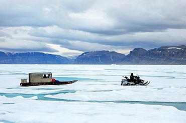 Inuit hunter driving snowmobile with Qamutik Inuit sledge on icepack, Arctic Bay, Baffin Island, Nunavut, Canada