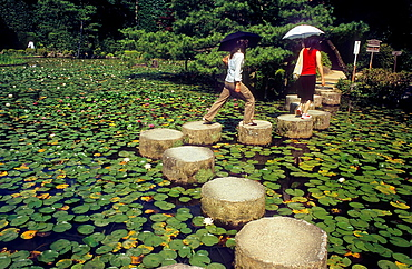 Tourists in garden of Heian Jingu sanctuary, Kyoto, Japan