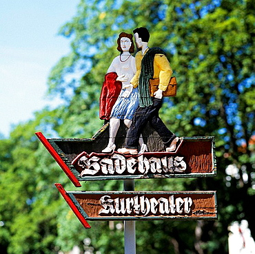 Germany, Bad Liebenstein, Grum brook, Werra Valley, nature reserve Thuringian Forest, Thuringian Forest, Thuringia, wood carved sign to the bath house and to the spa theatre, image of a young couple walking