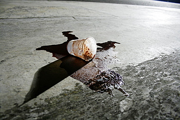 one spilled coffee cup in street road in city town at night
