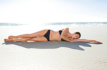 A female lying on the beach, A landscape shot of a female lying on the beach with one arm outstretched, and the sea in the background