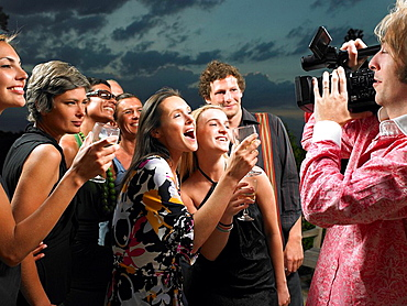 Man filming people at a cocktail party