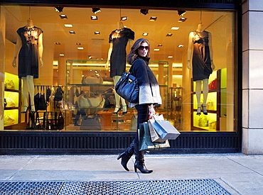 Woman with shopping in New York street, Elegant woman walking past shop window in New York, She is holding several shopping bags, looking at camera
