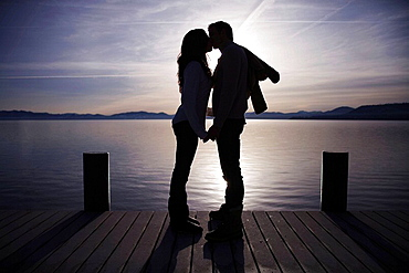 Couple kissing on pier at sunset