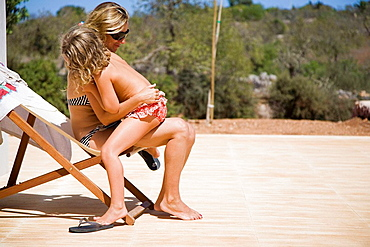 Mom hugs daughter, Mom hugs daughter outside on deck chair during vacation