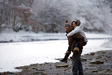 Couple walking in the snow, Couple walking in the snow, girl getting a piggy back