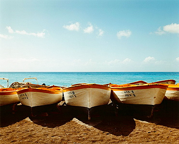 line of painted boats on beach, Wooden boats lined up on the beach at Positano, with sea behind