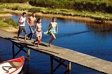 Group of young people running on jetty, Two teenage girls and two young men are running on jetty