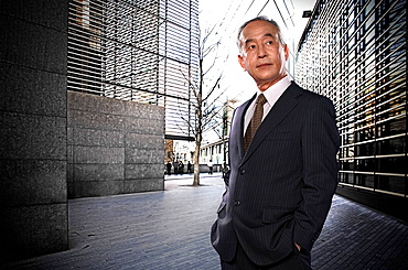 Businessman in city setting, hands in pockets, looking pensive