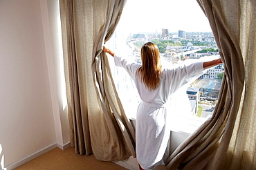 Woman in her bathrobe, opening curtains, Woman in her bathrobe, opening curtains