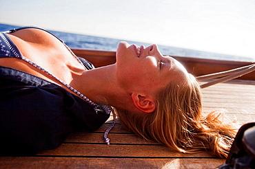 woman lying on deck eyes closed