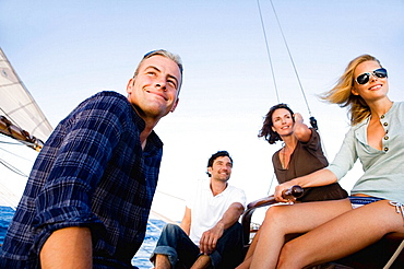two couples steering a sailing boat