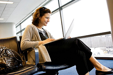 Woman checking email in airport, Middle age woman on lap top in airport checking email while traveling for business