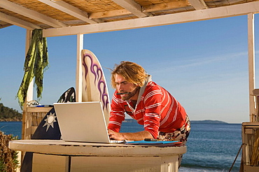 young man with laptop at beach house, young man with laptop at beach house