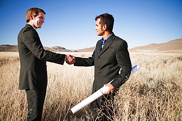 2 men with plans in field, shaking hands, 2 men with plans in field, shaking hands