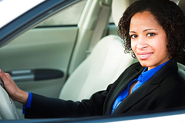 Woman in suit in car smiling, Woman in suit in car smiling