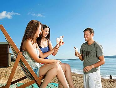 Friends enjoying ice cream by the sea