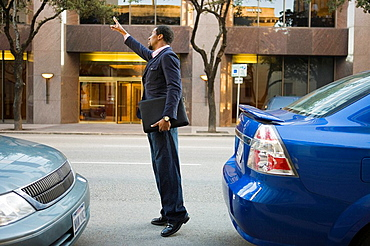 businessman signaling for taxi