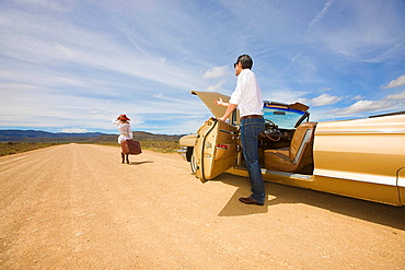 Couple with car trouble in desert, A couple, classic convertible, desert, middle on nowhere, she´s leaving