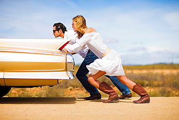 Couple pushing a car, Blond woman, dark haired man, classic convertible car, break down