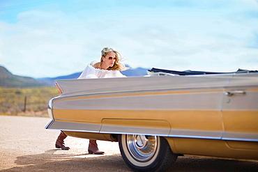 Woman pushing a car, Blond woman, classic convertible car, break down