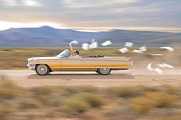 Couple celebrating freedom, Convertible car, young couple, flying paper
