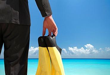 Businessman carrying fins on beach, Businessman carrying fins on beach