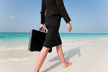 Businesswoman walking on tropical beach, Businesswoman walking on tropical beach