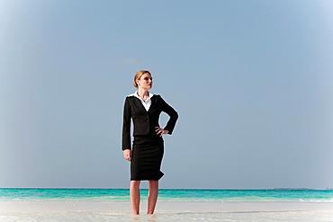 Businesswoman standing on tropical beach, Businesswoman standing on tropical beach