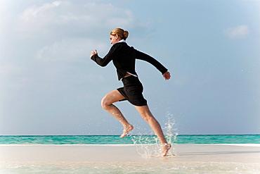 Businesswoman running on tropical beach, Businesswoman running on tropical beach