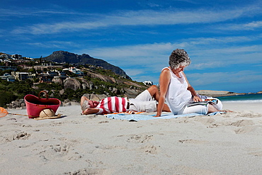 Older couple relaxing together on beach, Older couple relaxing together on beach