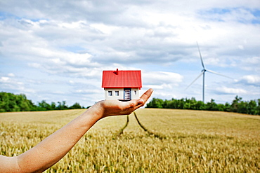 Woman with model house at wind turbines, Woman with model house at wind turbines
