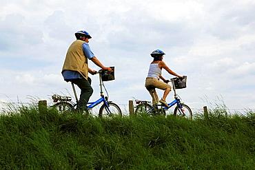 Route der Industriekultur, Ruhrtal, Tourismus, Freizeit, Fahrradausflug, zwei Radfahrer fahren auf dem Ruhrdeich, Mann, 50 bis 60 Jahre, Frau, 30 bis 40 Jahre, D-Muelheim an der Ruhr, Ruhrgebiet, Nordrhein-Westfalen, NRW, Route of Industrial Heritage