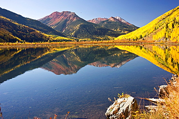 Rocky Mountain foliage reflects in a clear mountain lake