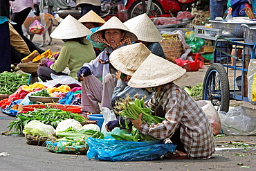 Women in conical hats selling vegetables sitting on street Binh Tay Market Cholon Ho Chi Minh City Vietnam