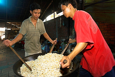 Two men with paddles mix popped rice and sugar to make rice candy crisp Mekong Delta Vietnam