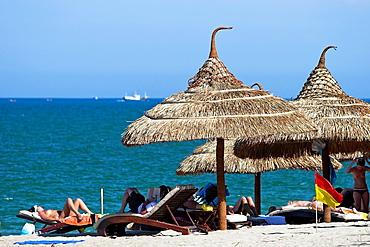 Holidaymakers relax under woven beach umbrellas Nha Trang south east Vietnam