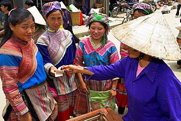 Flower Hmong young woman buy ice lollies from conical hat vendor Bac Ha hilltribe market north Vietnam