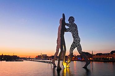 Molecule Man, sculpture by American artist Jonathan Borofsky, staging in the Spree river at sunset, overlooking the Oberbaumbruecke bridge, Friedrichshain and tv tower, Friedrichshain-Kreuzberg, Berlin, Germany
