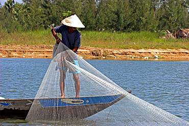 Conical hat man hand casting net fishing Thu Bon River in Hoi An historic town mid Vietnam