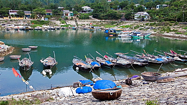 Woven coracles and traditional wooden boats harbor Cham Island off historic Hoi An Vietnam