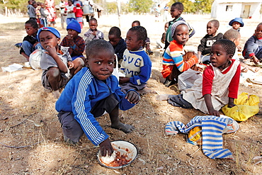 Children from school in Mpindo village in Zimbabwe are eating a bowl of sadza: a staple starch food made from meallie maize or corn, millet flour, stirred with water to a thick paste