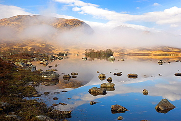 Rare combination of Clouds, Mirror Reflections, and Mist slowly clearing the Mountains on Loch na h Achlaise Rannoch Moor Highland Scotland