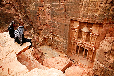 Bedouins sitting on top of a cliff looking down to the Treasury El Khazneh, Petra, Jordan