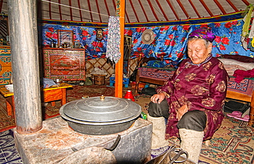 traditional nomad tends to the wood stove inside her ger in the Gobi Desert of Mongolia